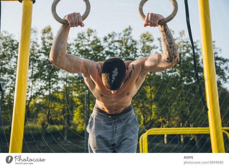 Athletischer junger Mann beim Vorbereiten und Kontrollieren von Gymnastikringen calisthenics Sport Ringe Muskeln Stärke Kunstturnen Straße Freestyle Körper