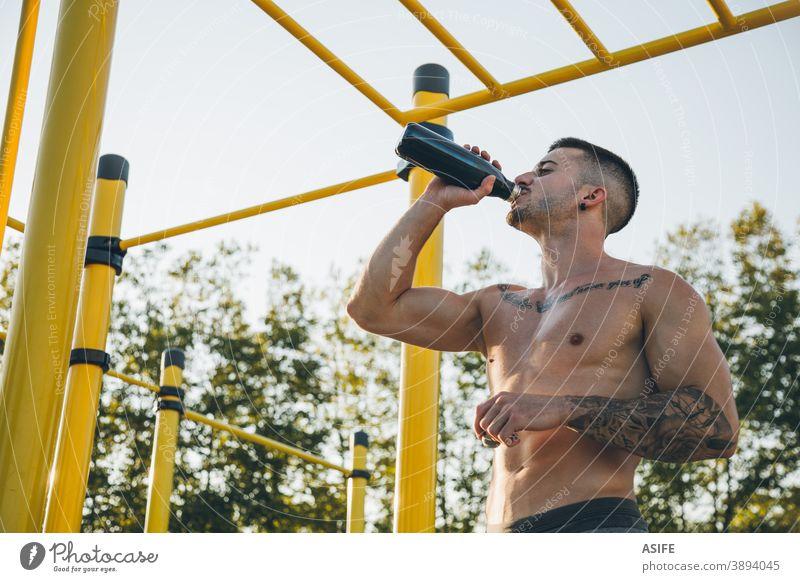 Junger Stadtsportler trinkt Wasser in einer Gymnastikhalle im Freien calisthenics Sport Athlet Mann trinken Flasche Muskeln Stärke Kunstturnen Straße Freestyle