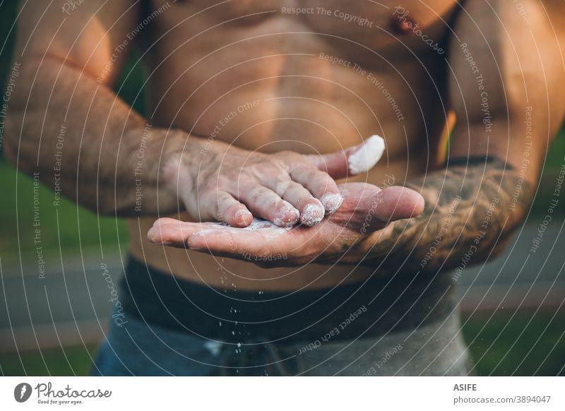 Junger städtischer Bodybuilder beschichtet seine Hände mit Magnesiumkreide für das Training von Gymnastikübungen Kreide calisthenics Pulver abschließen Sport