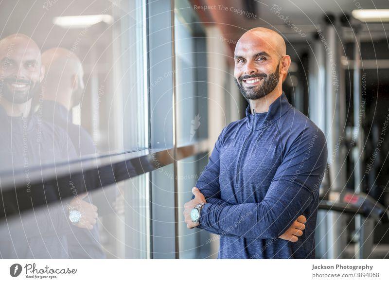 Porträt eines selbstbewussten, gut gebauten Mannes in der Turnhalle Trainerin Personal Fitnessstudio Lächeln Textfreiraum Bartiger Mann Vollbart Geschäftsmann