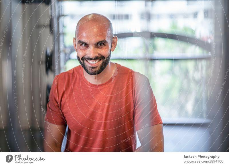 Verschwitzter Mann ruht sich zwischen den Trainingseinheiten im Fitnessstudio aus Sportler ruhen schweißtreibend Gebäude Zug Lächeln Blick Aktivität Schweiß
