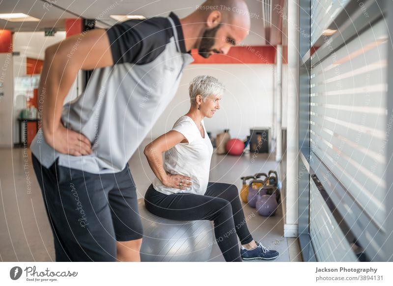 Schwangere Frau trainiert mit Personal Trainer schwanger Übung Fitnessstudio Trainerin Maschine trx Körperpflege Gewicht Unterleib Bauch im Innenbereich