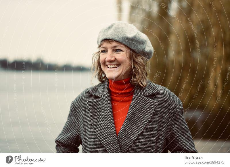 LACHEN - HERBST - MÜTZE - FRÖHLICH Frau 30 Jahre alt blond Locken Haare & Frisuren Baskenmütze Kopfbedeckung Fröhlichkeit Zufriedenheit lachen glücklich Wasser