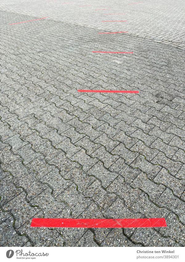 Abstand halten...  rote Striche als Markierungen auf grauem Steinpflaster | corona thoughts Markierungslinie Straße Corona Corona Virus Corona-Pandemie