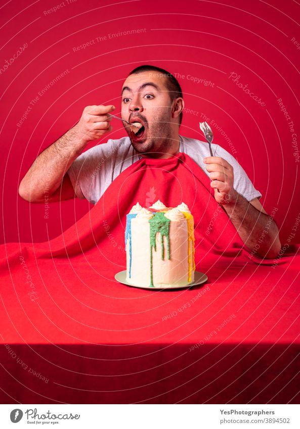 Mann isst allein Geburtstagskuchen. Gieriger Kerl isst einen riesigen Kuchen. Erwachsener Jahrestag Appetit & Hunger groß beide Hände Buttercremetorte zu feiern