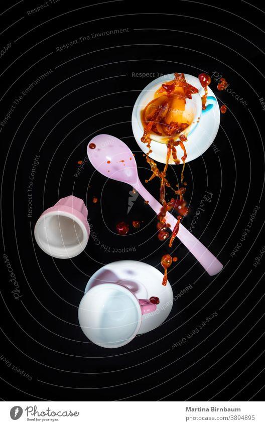 Herabfallende rosa Kaffeetassen und ein Löffel, Verschütten von Kaffee mit einem Spritzer platschen eingießen Bewegung heiß Tropfen Objekt Tasse trinken braun