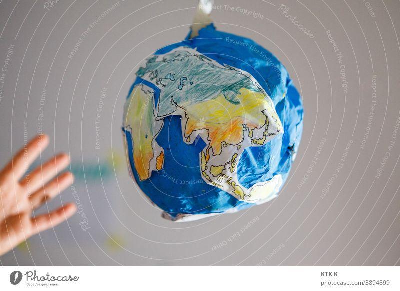 Die Welt zum Greifen nah; Pappwelt Erde Pappmodel Erde Pappmaché Model Modelbau Maßstab Fälschung Hand greifen Ozean Kontinente blau Wasser Globus Schulprojekt