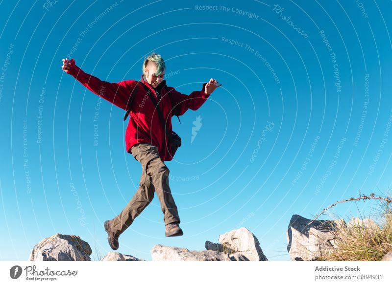 Fröhlicher Wanderer beim Trekking in den Bergen Hochland springen extrem Adrenalin Nachlauf Felsen Energie Berge u. Gebirge El Mazuco Asturien Spanien reisen