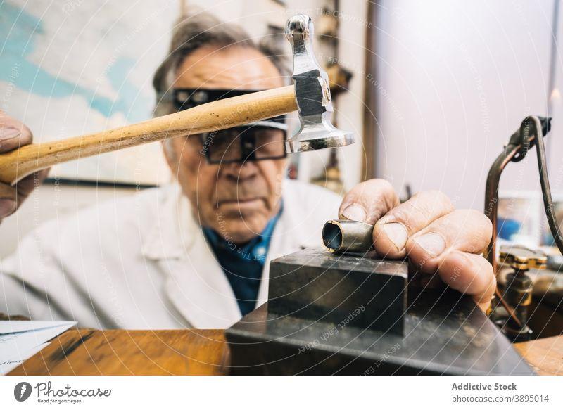 Juwelier mit Hammer und Meißel beim Erstellen von Schmuck in der Werkstatt Beitel Edelstein Arbeit professionell Mann Werkzeug Fähigkeit reif männlich Meister
