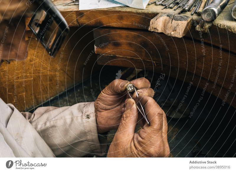 Juwelier bei der Arbeit mit Diamanten in der Werkstatt professionell Mann Goldschmied Stein Pinzette Fähigkeit reif Werkzeug männlich Meister Hobelbank Schmuck
