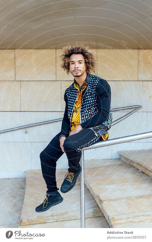 Stilvolle Hipster ethnischen Mann sitzt auf Geländer trendy informell Mode krause Haare Vollbart jung modern Outfit Schritt Reling Typ Afroamerikaner schwarz