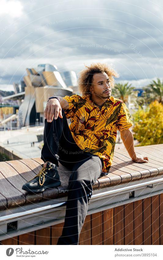 Selbstbewusst trendy Hipster Mann ruht auf der Straße Stil informell Mode krause Haare Vollbart jung modern farbenfroh Outfit Typ Afroamerikaner schwarz