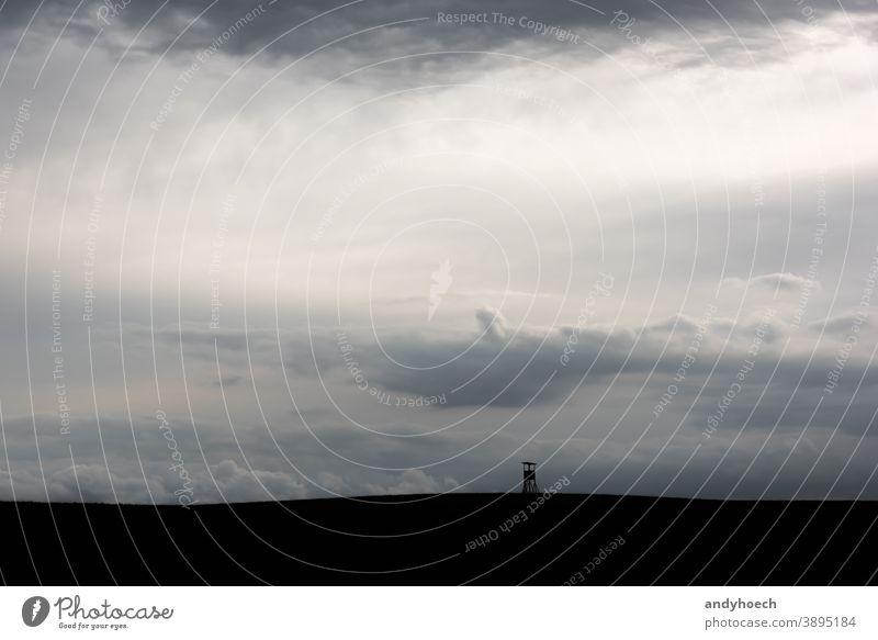 Silhouette eines Hochsitzes in dichten Wolken abstrakt Kunst Hintergrund schön schwarz Boxenständer wolkig Textfreiraum Hirsch-Stand Feld Rahmen Spiel Tierhaut