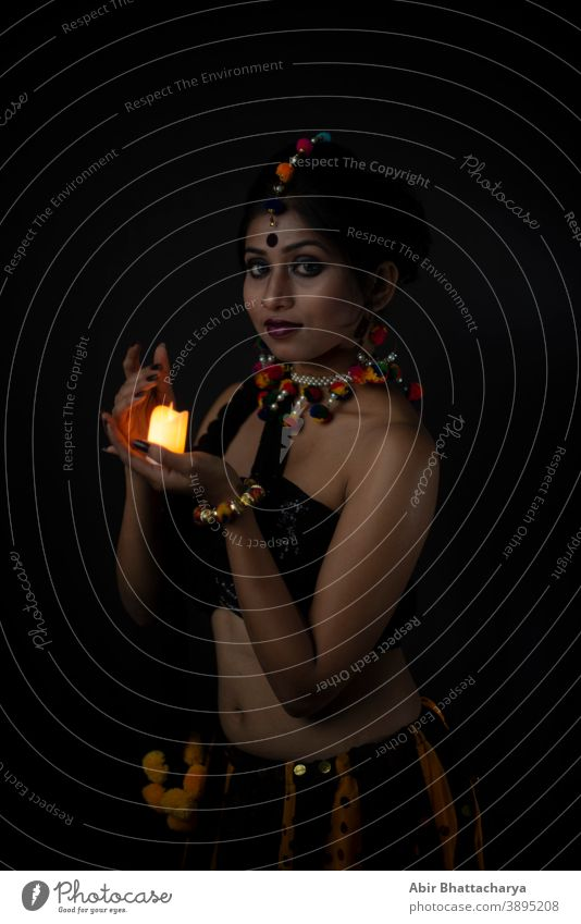 Bildnis einer indisch-bengalischen brünetten Frau in traditioneller indischer Stammes-/Dorfbewohner-Kleidung und handgemachten Ornamenten mit Kerze in dunklem Kopierraum-Atelierhintergrund. Indische Lifestyle- und Modefotografie.