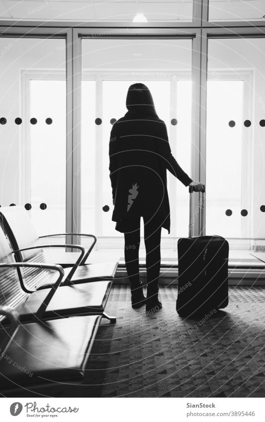 Junge Frau auf dem Flughafen, die durch das Fenster auf Flugzeuge schaut reisen s/w schwarz weiß Terminal Mädchen Gepäck Abheben Transport Ebene Ausflug