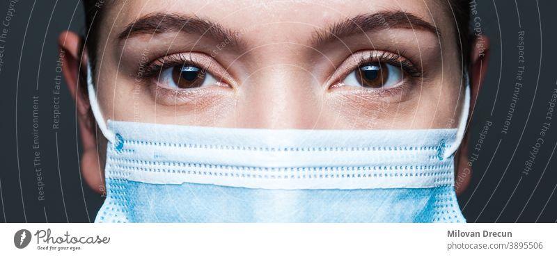 Junge kaukasische Frau mit blauer chirurgischer Gesichtsmaske Nahaufnahme-Breitbildportrait Coronavirus covid-19 Porträt Auge Mundschutz Arzt Transparente