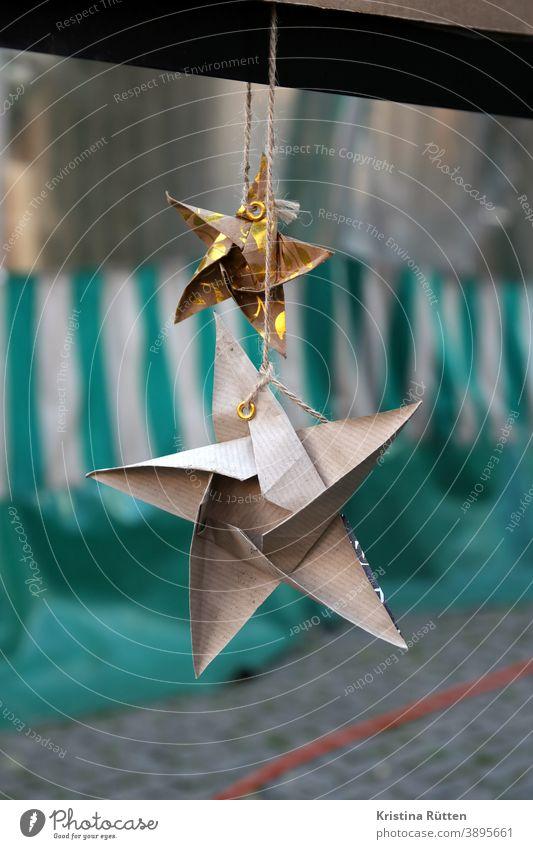 selbstgebastelte papiersterne als deko an marktstand weihnachtsschmuck weihnachtsdeko weihnachtlich origami selbsgebastelt basteln weihnachten dekoration