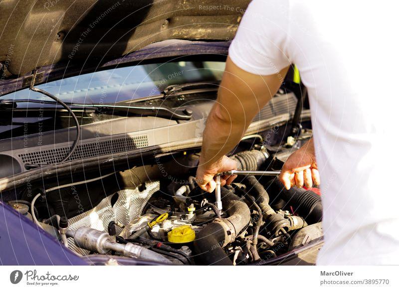 Der Mechaniker repariert den Automotor Überprüfung eines Automotors Eninge-Reparatur Motorschaden Autopflege Automechanikerin Kraftfahrzeugmechaniker