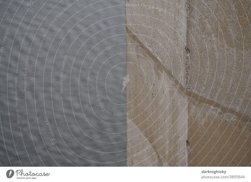 Beton Pfeiler mit Ecke in beigen und grauen Farbtönen vor einem Hintergrund aus Wasser Außenaufnahme Architektur Farbfoto Brücke pfeiler Wand Menschenleer