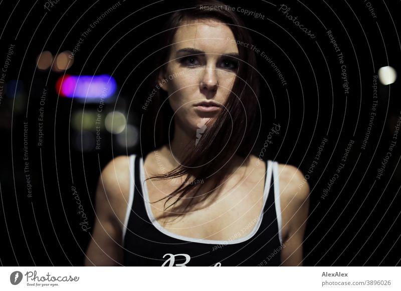 Portrait einer jungen Frau Stadtlichtern in der Nacht junge Frau draussen Nachtleben Nachtstimmung nahe Nähe Kälte Licht Trägertop langhaarig brünett schlank
