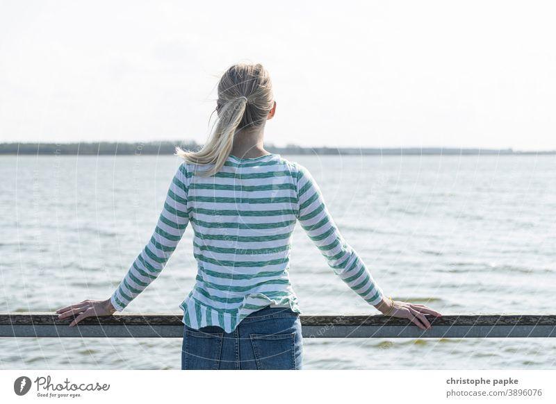 Blonde Frau steht an Rehling und blickt aufs Meer blond Rückansicht Urlaub Ostsee Bodden Boddenlandschaft Mecklenburg-Vorpommern entspannen ausblick genießen