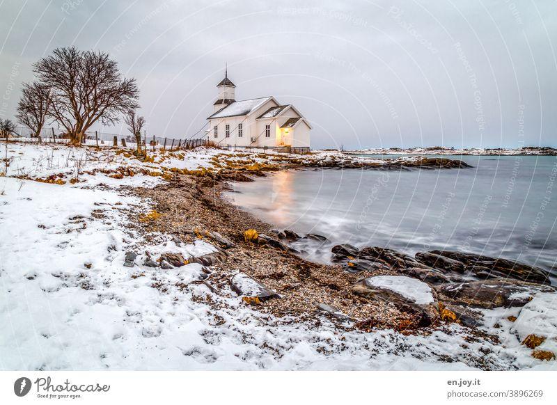Gimsoy Kirche auf den Lofoten Gimsøy Strand Meer Bucht Schnee Winter Norwegen Skandinavien Baum Felsen Langzeitbelichtung Abend blaue Stunde Himmel Küste kalt