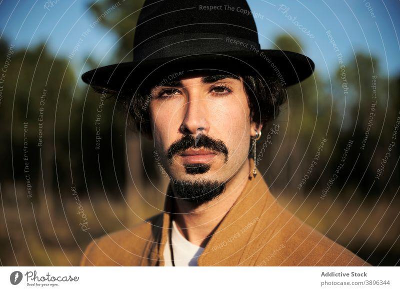 Stilvoller Mann mit Hut auf einer Wiese stehend Hipster Vollbart Reisender Piercing jung männlich trendy modern gutaussehend selbstbewusst Vorschein