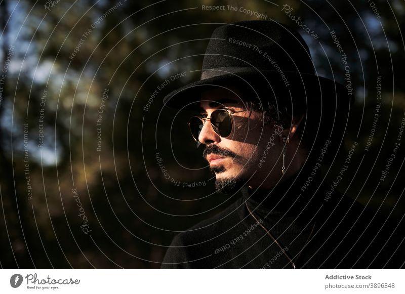 Stilvoller Mann mit Hut und Sonnenbrille auf der Wiese stehend Hipster Vollbart Reisender Piercing jung männlich trendy modern gutaussehend selbstbewusst Brille