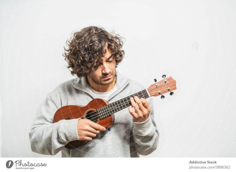 Fröhlicher Mann spielt Ukulele Gitarre spielen heiter Musiker ausführen positiv Instrument Glück jung ethnisch hispanisch männlich Melodie Lifestyle Gesang