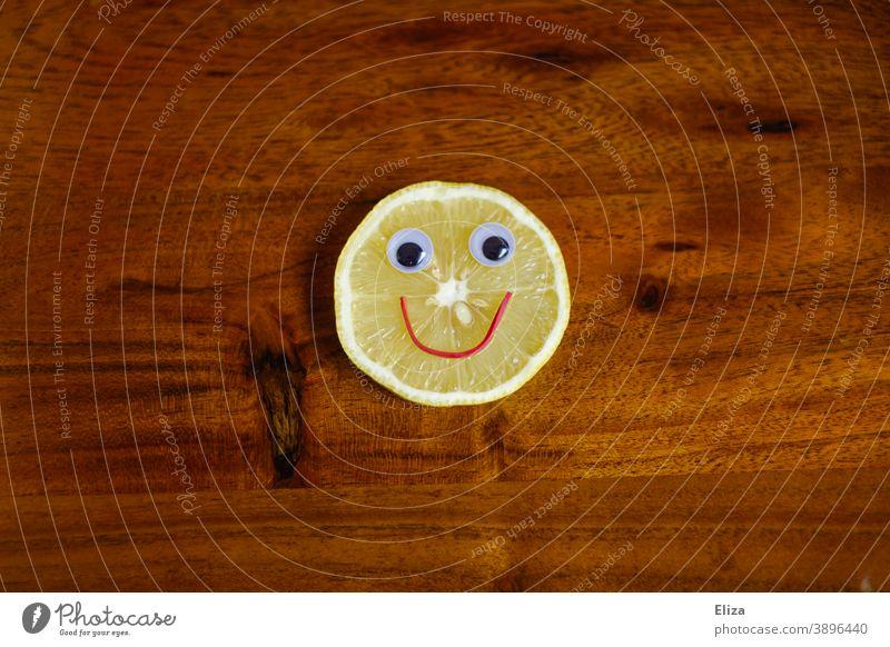 Sauer macht lustig - Zitronenscheibe mit lachendem Gesicht auf Holz sauer fröhlich Vitamine gesund Vitamin C gelb Lebensmittel vitaminreich gute Laune rund