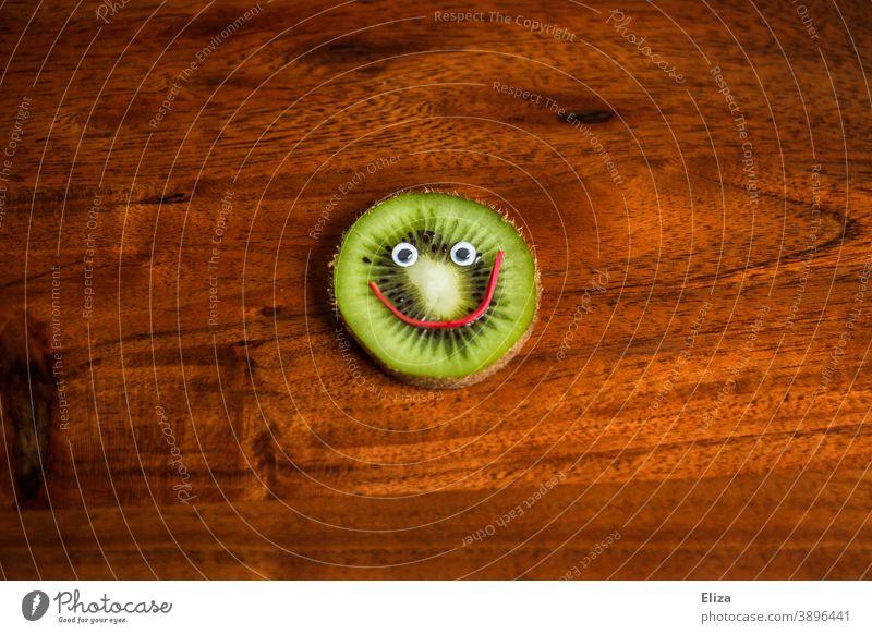 Eine Scheibe Kiwi mit lachendem Gesicht - Gesunde Ernährung gesund Vitamine Vitamin C Frucht Obst vitaminreich fruchtig lustig grün rund Holz