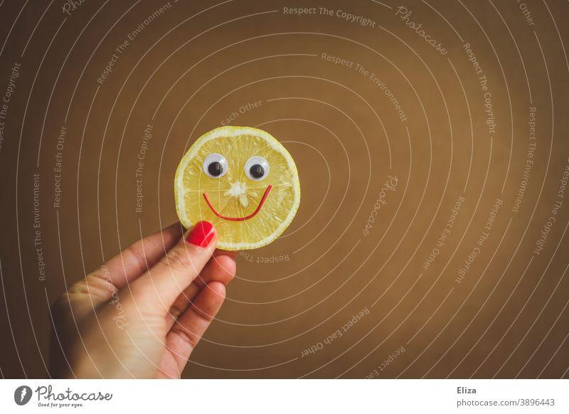 Sauer macht lustig  - Eine Hand hält eine Zitronenscheibe mit lachendem Gesicht sauer fröhlich Vitamine gesund Vitamin C gelb Lebensmittel vitaminreich