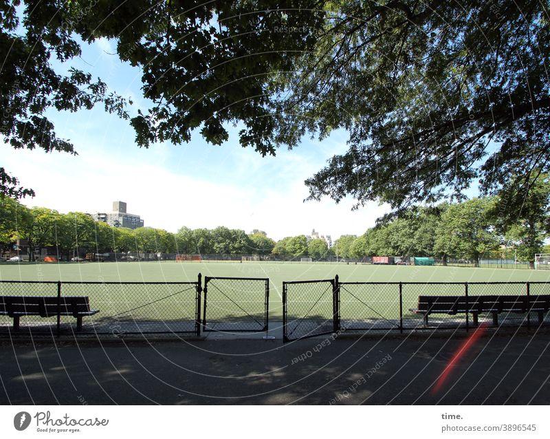 Geschichten vom Zaun (97) sportplatz park zaun tor gatter einlass sonnig bank schatten baum Schönes Wetter hochhaus bäume freizeit erholung