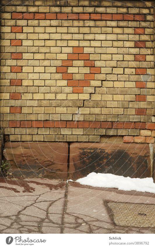 Letzter Schnee vor einer Backsteinmauer mit treppenförmigem Riss Mauer Backsteine Schafe Asphalt hintergrund verrotten beige Risse Buntsandstein Sandsteinblöcke