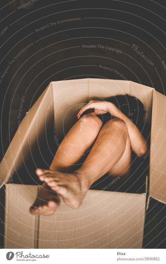 Eine nackte Frau zusammengekauert in einer Kiste Karton umzugskiste Versandkarton Menschenhandel Ware Mensch Paket schutzlos Verpackung ausgeliefert ungemütlich