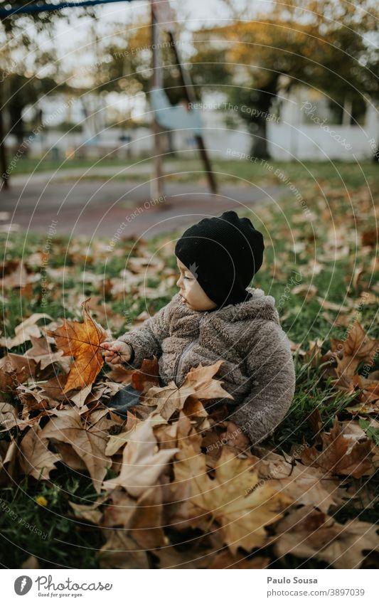 Kleinkind spielt mit Herbstblättern Kind Kindheit Kaukasier 1-3 Jahre Mensch Farbfoto Außenaufnahme Fröhlichkeit Glück Tag Lifestyle Freude authentisch