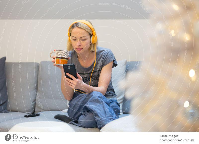Junge fröhliche Frau, die zu Hause auf dem Wohnzimmersofa sitzt, soziale Medien am Telefon für Videochats nutzt und mit ihren Lieben in Verbindung bleibt. Zu Hause bleiben, sozial distanzierender Lebensstil