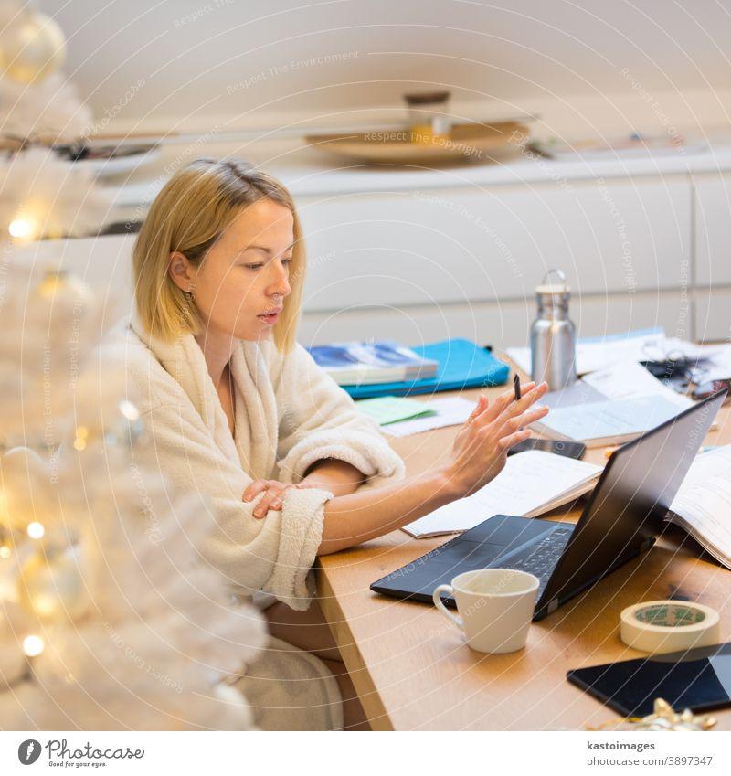 Junge Unternehmerin im kuschelig warmen Bademantel bei der Arbeit fern von zu Hause in der winterlichen Weihnachtszeit während der Coronavirus-Pandemie 2020. Arbeit von zu Hause aus, selter an Ort und Stelle, Konzept.