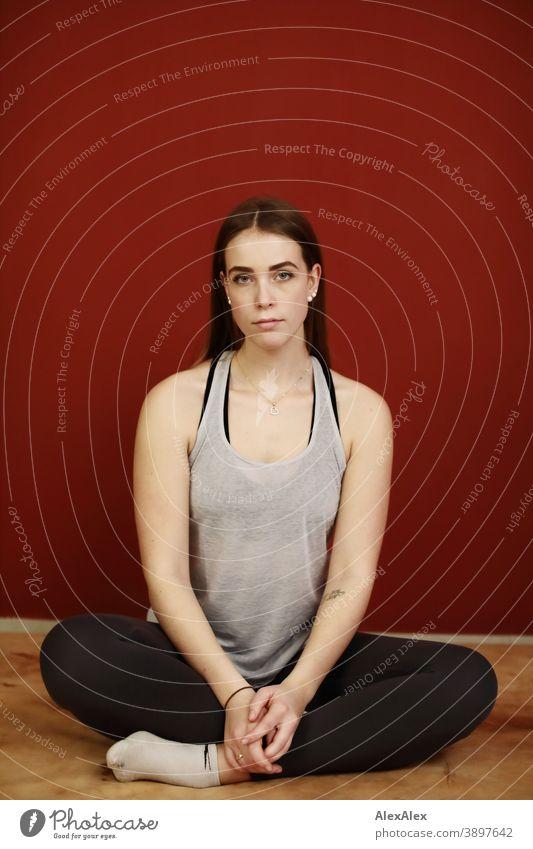 Portrait einer jungen, sportlichen Frau in Sportsachen in einem Raum vor roter Wand Studentin anmutig Schmuck Gesichtsausdruck Empathie Blick in die Kamera