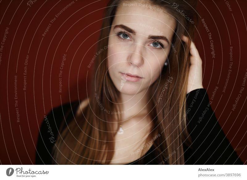 Portrait einer jungen Frau in einem Raum mit roter Wand Studentin anmutig Schmuck Gesichtsausdruck Empathie Blick in die Kamera Textfreiraum links Nahaufnahme