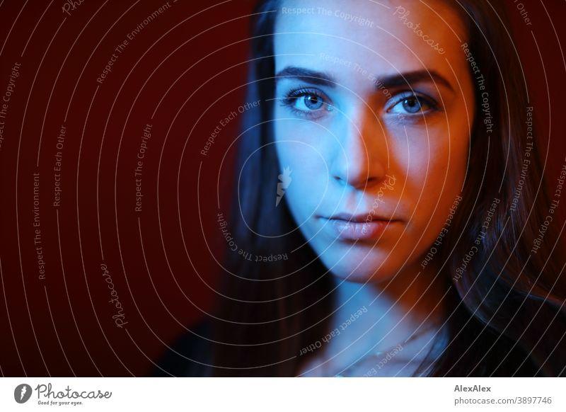 Portrait einer jungen Frau in einem Raum vor roter Wand mit rotem und blauem Licht Studentin anmutig Gesichtsausdruck Empathie Blick in die Kamera