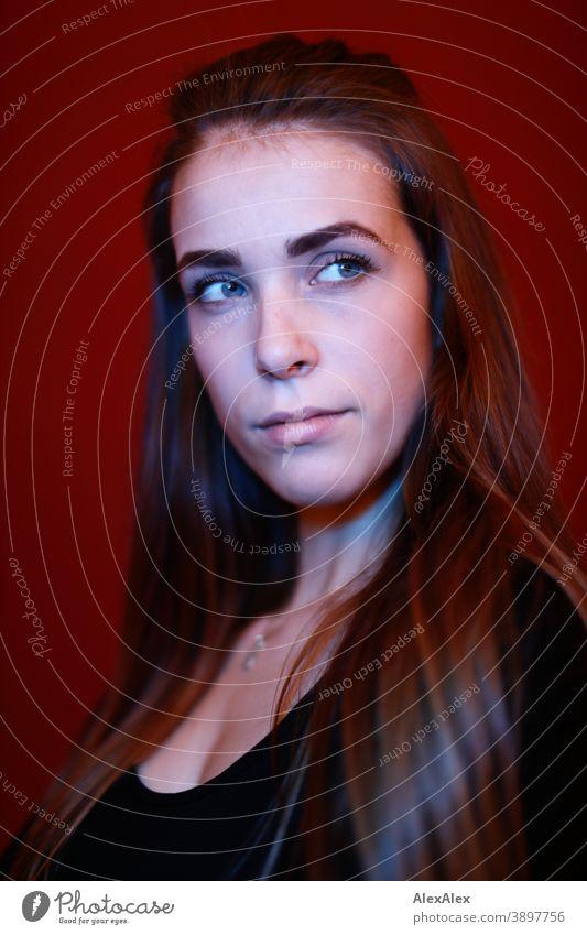 Portrait einer jungen Frau in einem Raum vor roter Wand mit rotem und blauem Licht Studentin anmutig Schmuck Gesichtsausdruck Empathie Blick in die Kamera