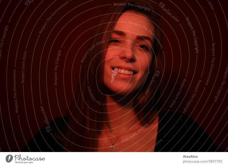 Portrait einer jungen Frau in einem Raum mit rotem Licht Studentin freundlich anmutig Schmuck Gesichtsausdruck Empathie Blick in die Kamera Textfreiraum links