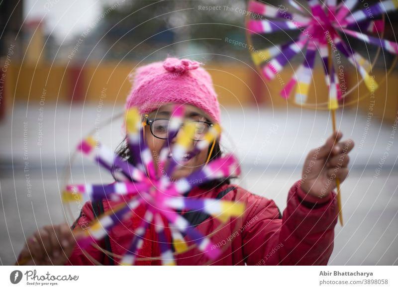 Ein fröhliches indisch-bengalisches brünettes Mädchen in Winterjacke und Wollmütze genießt das Schwungrad am Winternachmittag auf dem Dach. Indischer Lebensstil