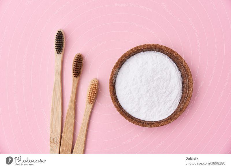 Drei hölzerne Bambus-Zahnbürsten und Backpulver auf rosa Hintergrund, Draufsicht Soda Pflege mündlich backen Produkt Bürste natürlich Hygiene organisch Natur