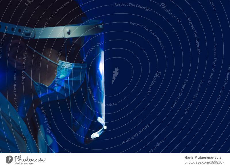 Ärztin mit Gesichtsschutz und Maske Seitenansicht auf dunkelblauem Hintergrund schwarzer Hintergrund Brasilien Korona-Epidemie Corona-Virus covid-19