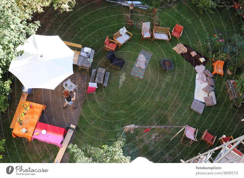 Blick von oben in einen Garten mit Tischen, Stühlen und Matratzen für eine Gartenparty Gartenfest Sommerfest Fest Party Gäste leer vorbereitet gerichtet