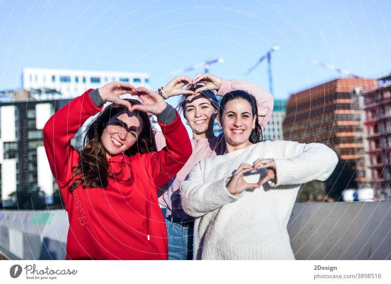 Porträt von drei jungen Frauen, die lächelnd mit Fingergesten ihr Herz zeigen Mädchen im Freien Liebe Bonden Nähe Freundschaft gestikulierend flirten