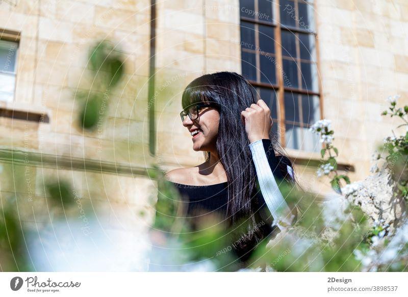 Porträt einer schönen jungen Frau, die lächelnd in die Kamera blickt, während sie auf der Straße steht. im Freien Person Lifestyle Brille Glück Mädchen Stehen