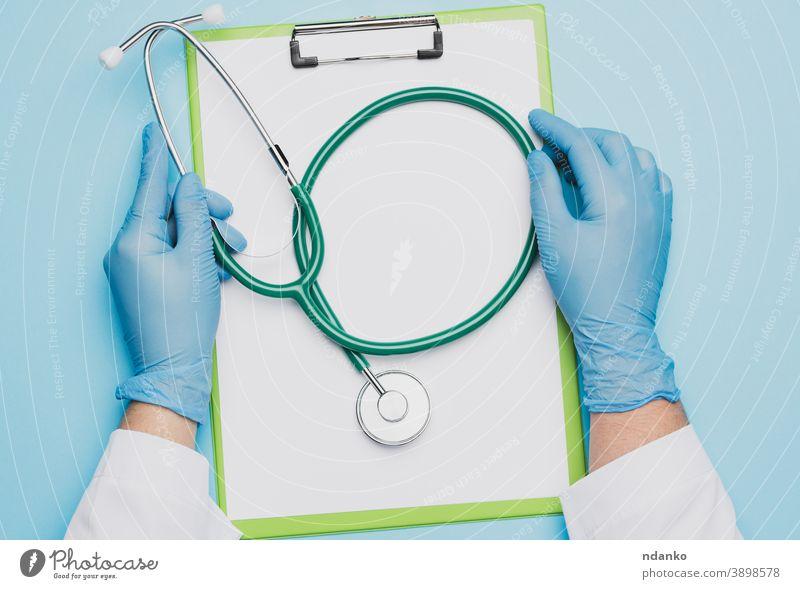 die Hände einer Ärztin in blauen Latexhandschuhen, die ein Metallstethoskop halten Papier Stethoskop Chirurg Werkzeug Behandlung Zwischenablage Frau Arbeiter